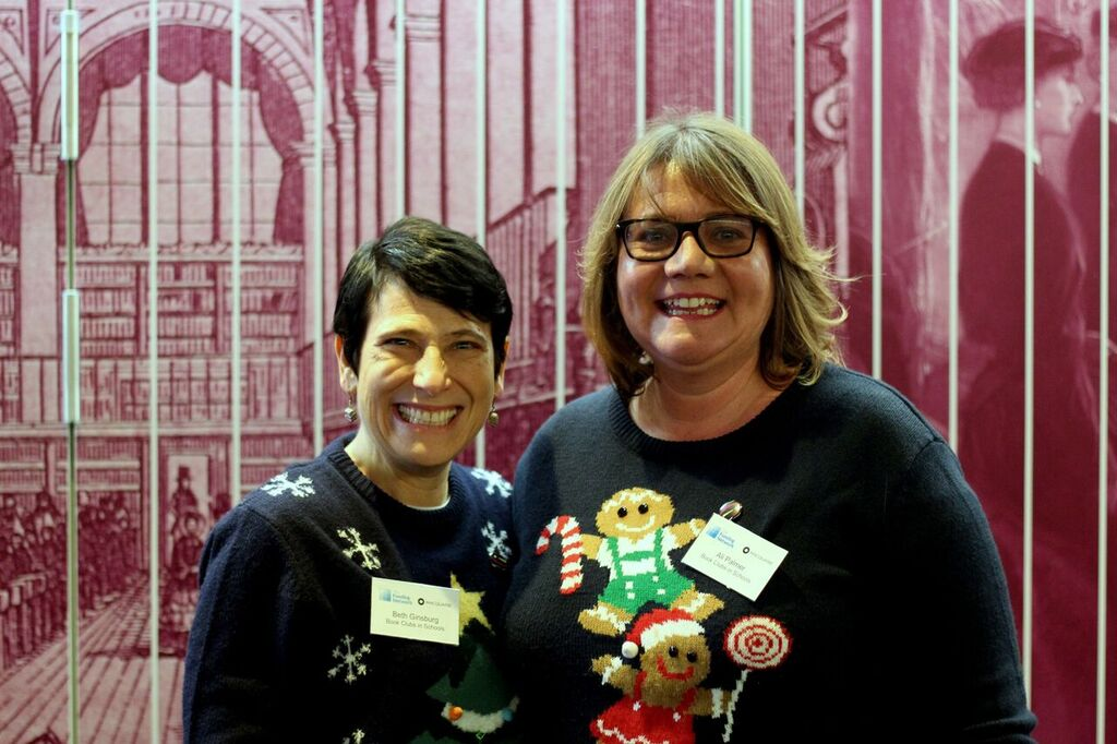 Photo of Beth Ginsburg and Ali Palmer, co-founders of Book Clubs in Schools, wearing jumpers and standing in front of a red background at a The Funding Network event