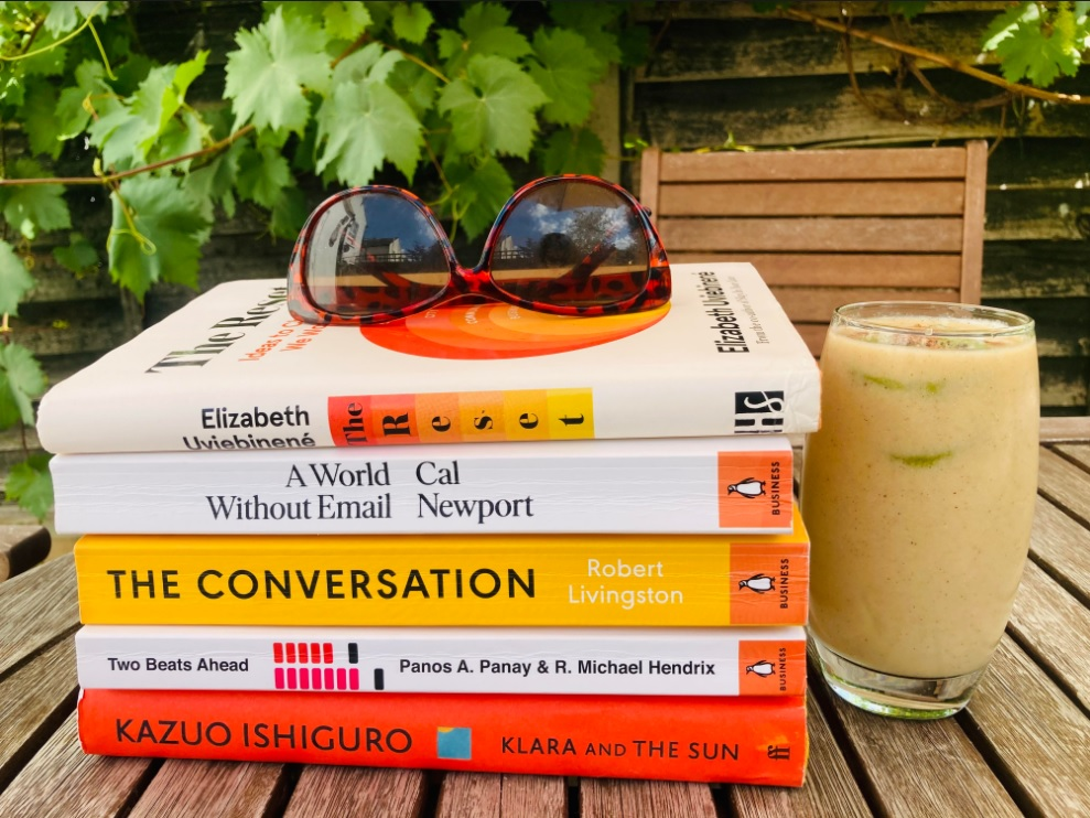 Picture of books on garden table with a pair of sunglasses on top